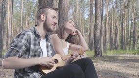 Portret knappe gebaarde jonge man het spelen ukelele terwijl vrij jonge gelukkige vrouwenzitting dichtbij Houdend van paar die he stock videobeelden