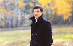 Portret knappe glimlachende mens die een zwart laagjasje in de zonnige herfst dragen royalty-vrije stock afbeeldingen