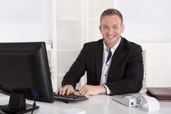 Portret: Knappe jonge zakenman die in kostuumzitting binnen glimlachen Royalty-vrije Stock Foto