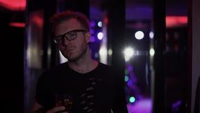 Portret knappe ontspannen mens die zich met dicht omhoog glas van alcohol bij de disco bevinden Mens die in glazen camera bekijkt stock video
