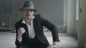 Portret knappe zekere mens in een hoed die het muntstuk in de vingers draait die in een verlaten gebouw zitten Het hoofd van stock videobeelden