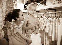 Portret kobieta i dziewczyna robi zakupy białą dziecko odzież w płótnie Fotografia Stock