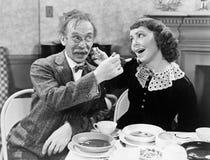 Portret kobieta i mężczyzna żywieniowa polewka each inny przy stołem (Wszystkie persons przedstawiający no są długiego utrzymania Fotografia Stock