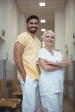 Portret kobieta i męska pielęgniarki pozycja w korytarzu Obraz Royalty Free