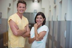 Portret kobieta i męska pielęgniarki pozycja w korytarzu Obrazy Royalty Free