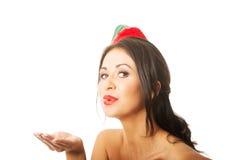 Portret kobieta jest ubranym elfa dmuchania odzieżowego buziaka, patrzeje kamerę Zdjęcie Royalty Free