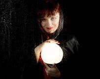 Portret kobieta model, pozuje za przejrzystym szkłem zakrywającym wodnymi kroplami kobiety mienia wielka rozjarzona piłka Zdjęcia Stock