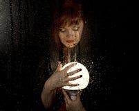 Portret kobieta model, pozuje za przejrzystym szkłem zakrywającym wodnymi kroplami kobiety mienia wielka rozjarzona piłka Obraz Royalty Free