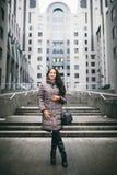 Portret kobieta na biznesowym temacie Młoda Kaukaska brunetki dziewczyna w długiej kurtce, żakiet z czarnymi rzemiennej torby sto zdjęcie stock