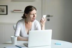 Portret kobieta przy biurkiem z laptopem, patrzeje wiszącą ozdobę Obrazy Royalty Free