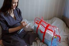 Portret kobieta w ciąży na łóżku z listą kontrolną i torby ludźmi opłaty szpital obraz royalty free