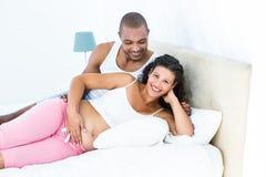Portret kobieta w ciąży z męża lying on the beach na łóżku zdjęcia stock
