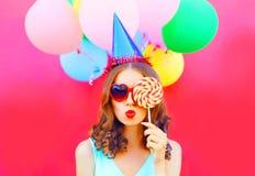 Portret kobieta w urodzinowej nakrętce dmucha wargi jest zakończeniami jej oko z lizakiem na kiju nad lotniczy kolorowi balony obraz stock