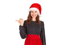 Portret kobieta wskazuje z lewej strony z kciukiem i ono uśmiecha się w sukni emocjonalna dziewczyna w Santa Claus bożych narodze obrazy royalty free