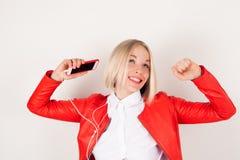 Portret kobieta z hełmofonami i telefonem komórkowym w ręce w czerwonej kurtce na białym tle Zdjęcia Stock