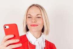 Portret kobieta z hełmofonami i telefonem komórkowym w ręce w czerwonej kurtce na białym tle Fotografia Royalty Free