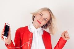 Portret kobieta z hełmofonami i telefonem komórkowym w ręce w czerwonej kurtce na białym tle Obraz Stock