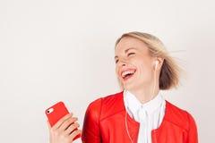 Portret kobieta z hełmofonami i telefonem komórkowym w ręce w czerwonej kurtce na białym tle Obrazy Royalty Free