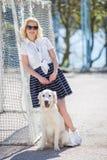 Portret kobieta z pięknym psem bawić się outdoors Obrazy Stock