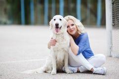 Portret kobieta z pięknym psem bawić się outdoors Obraz Stock