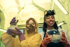 Portret kobiety trzyma kolbę i puchar z odczynnikami w laboratorium w mundurach Obrazy Royalty Free