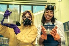 Portret kobiety trzyma kolbę i puchar z odczynnikami w laboratorium w mundurach Fotografia Royalty Free