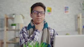 Portret koude jonge Aziatische mens in een overhemd met keelpijnzitting bij laptop stock videobeelden