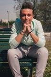 Portret krótkiego włosy dziewczyny obsiadanie na ławce Obraz Stock