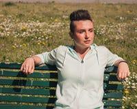 Portret krótkiego włosy dziewczyny obsiadanie na ławce Zdjęcie Stock