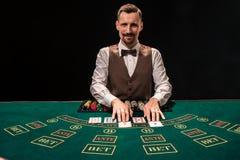 Portret krupier trzyma karta do gry, uprawia hazard szczerbi się na stole Czarny tło obrazy royalty free