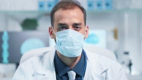 Portret lekarka jest ubranym leczniczą maskę i patrzeje kamerę zdjęcie wideo