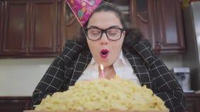 Portret leuk vet gelukkig meisje in een feestelijk GLB en modieuze glazen die bij de lijst in de keuken en het blazen a zitten stock video