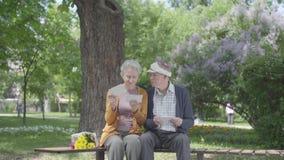 Portret leuk volwassen paar die oude foto's die gelukkige ogenblikken herinneren die op een bank in het park zitten kijken Rijp p stock footage