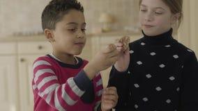 Portret leuke Afrikaanse Amerikaanse jongen en blond Kaukasisch meisje die met blauwe ogen in de keuken spelen Kleine gelukkige v stock footage