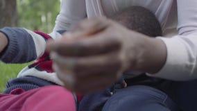 Portret leuke Afrikaanse Amerikaanse vrouw die met haar weinig zoon spelen die plastic stuk speelgoed in het park gebruiken De jo stock video