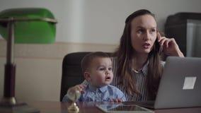 Portret leuke bezige jonge moeder die thuis met de baby aan haar overlappingen werken De vrouw die door cellphone spreken terwijl stock videobeelden