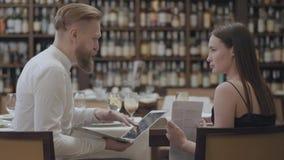 Portret leuke donkerbruine vrouw en blonde gebaarde man zitting bij de lijst in de koffie die informatie over laptop bespreken stock videobeelden