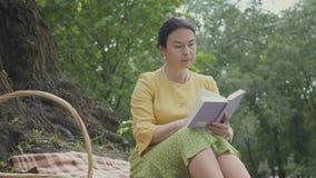 Portret leuke elegante mooie rijpe vrouw die de boekzitting op de deken leest onder de boom in het park rijs stock footage
