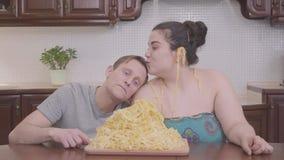 Portret leuke mollige vrouw en magere blonde man in de keuken bij de lijst voor grote plaat met noedels De man stock videobeelden