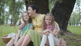 Portret leuke rijpe vrouw die haar twee leuke kleindochters kussen die op het gras onder de boom in het park, het kijken zitten stock footage
