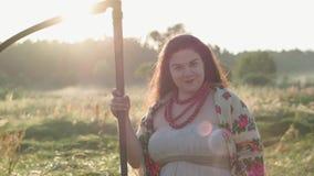 Portret leuke te zware vrouw die een zeis houden bekijkend camera op het groene de zomergebied in zonlicht Mooi stock videobeelden