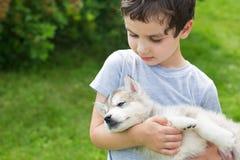 Portret śliczna chłopiec z sypialnym łuskowatym szczeniakiem Zdjęcie Stock