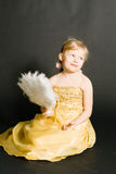 Portret of little girl in yellow dress. Sitting stock image