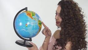 Portret młoda piękna kędzierzawa dziewczyna z kreatywnie uzupełnia pokrętną kulę ziemską z zabawą i ładnym uśmiechem zbiory wideo
