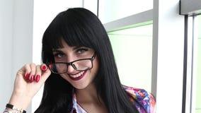 Portret młoda piękna szczęśliwa kobieta stoi blisko okno z szkłami, patrzeje kamery ono uśmiecha się zdjęcie wideo