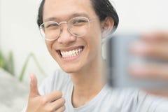 Portret młody atrakcyjny mężczyzna bierze obrazkom on jaźń lub selfie podczas gdy daje kciukowi w górę obraz royalty free