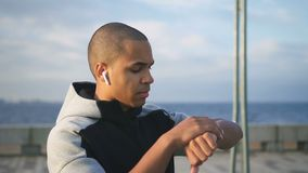Portret młody mieszany biegowy amerykanin afrykańskiego pochodzenia mężczyzny model patrzeje w ekranie jego mądrze gadżet dokąd z zdjęcie wideo