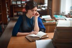 Portret mądry uczeń w bibliotece uniwersyteckiej zdjęcie royalty free