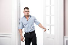 Portret mądrze poważna seksowna młody człowiek pozycja w drzwi domu wnętrzu Zdjęcia Royalty Free