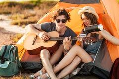 Portret mężczyzna bawić się gitarę dla jego dziewczyna campingu Zdjęcie Stock